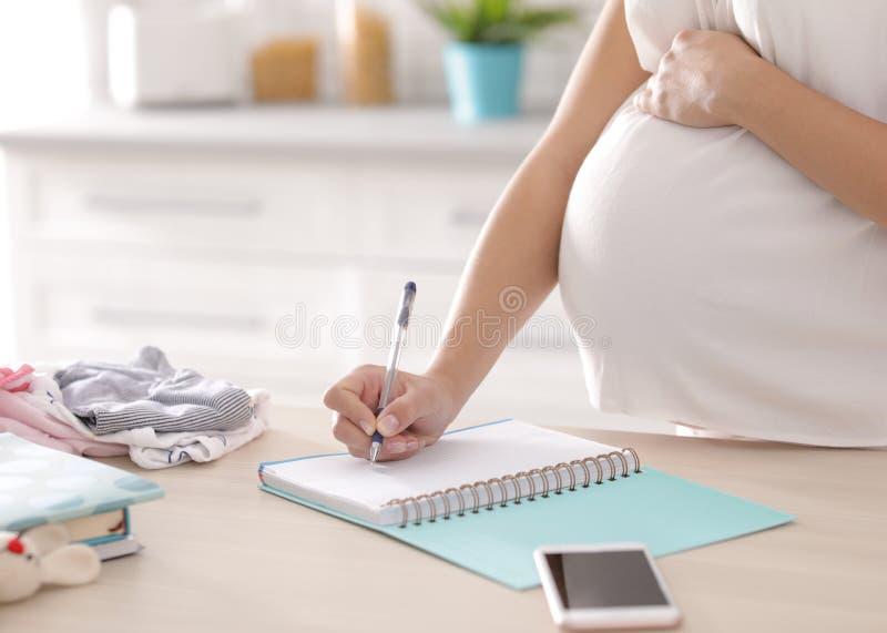 Donna incinta che redige la lista di imballaggio per la maternità nella cucina immagine stock