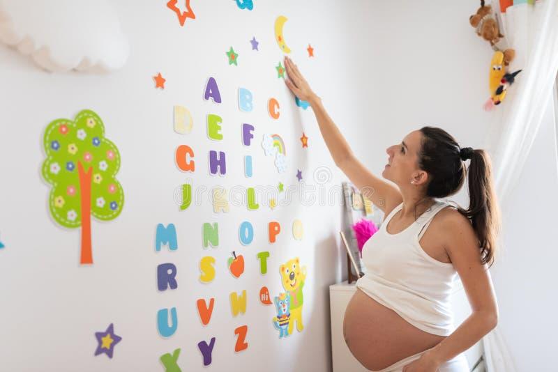 Donna incinta che segna la parete con lettere della stanza del bambino immagini stock