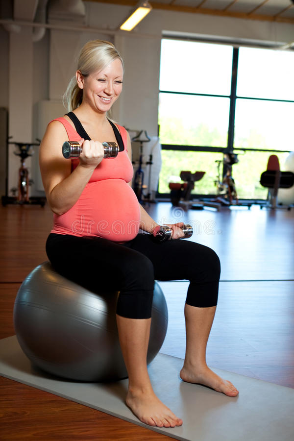 Donna incinta che si esercita con i pesi fotografia stock