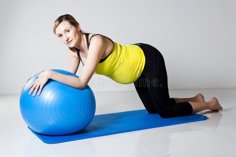 Donna incinta che si esercita con la sfera di forma fisica immagine stock libera da diritti