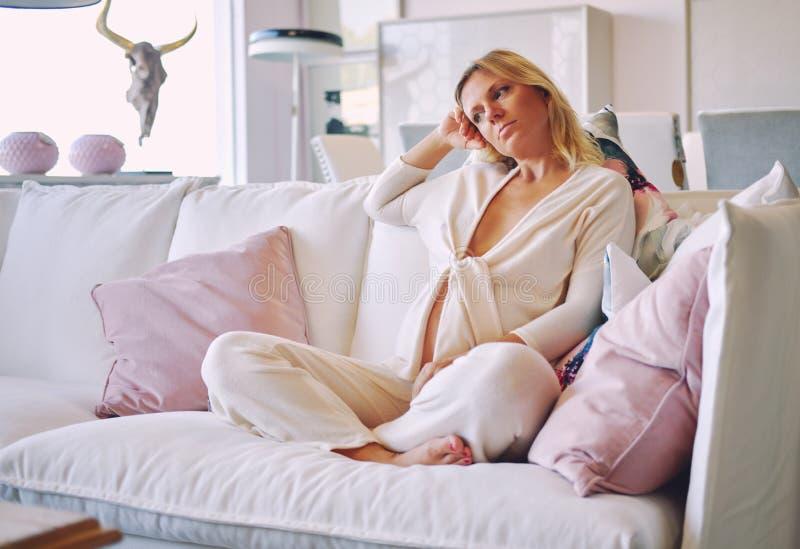 Donna incinta che si siede in strato alla stanza del salotto Giovane femmina annoiata pensierosa e seria bionda in vestito da mat fotografia stock libera da diritti