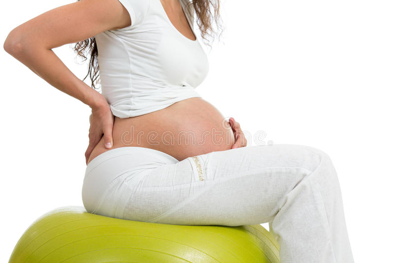 Donna incinta che si siede sulla palla di misura con la mano su lei indietro fotografie stock