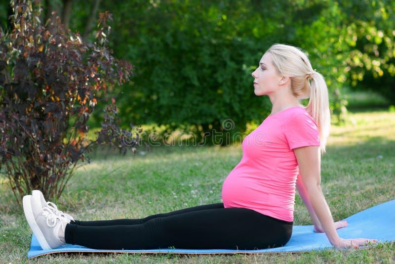 Donna incinta che si siede sulla vista laterale del karemat immagini stock libere da diritti