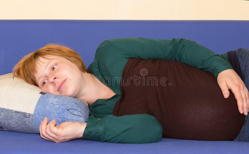 Donna incinta che si trova su un pensiero del sofà immagine stock libera da diritti