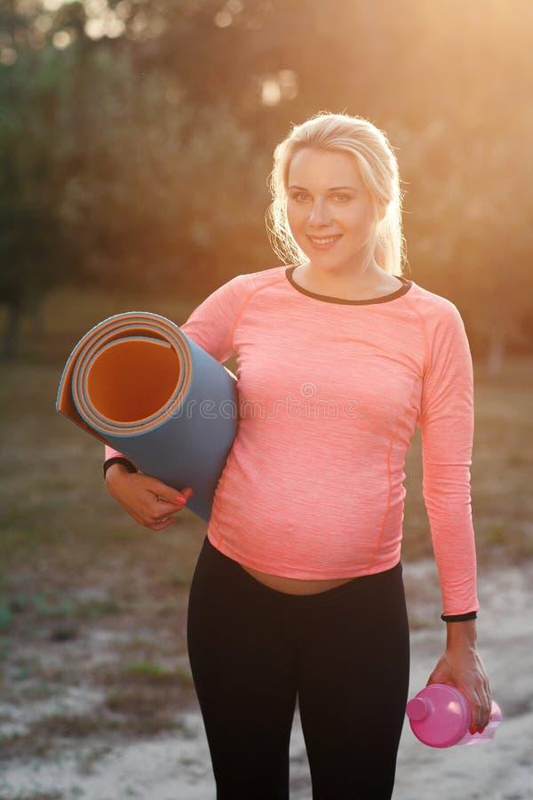 Donna incinta che sorride alla macchina fotografica, chiarore del sole immagini stock