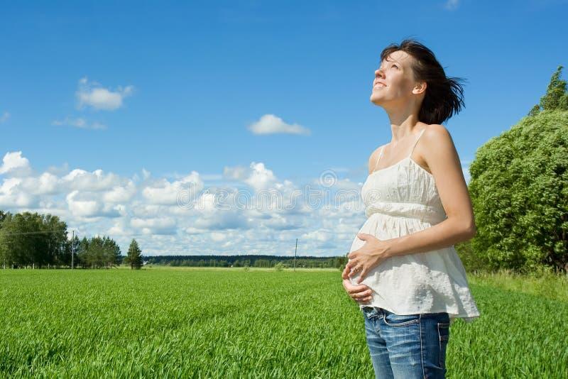 Donna incinta che sorride sul campo fotografia stock libera da diritti