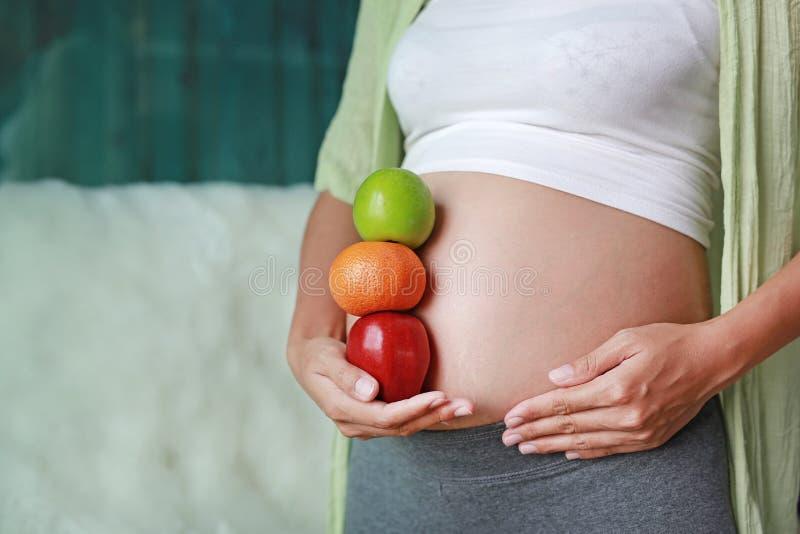 Donna incinta che tiene Apple Verde-rosso e frutta arancio alla sua pancia Concetto stante fotografie stock libere da diritti