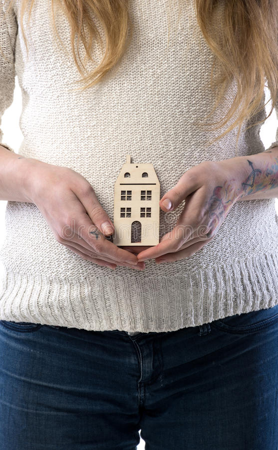 Donna incinta che tiene casa di legno immagine stock