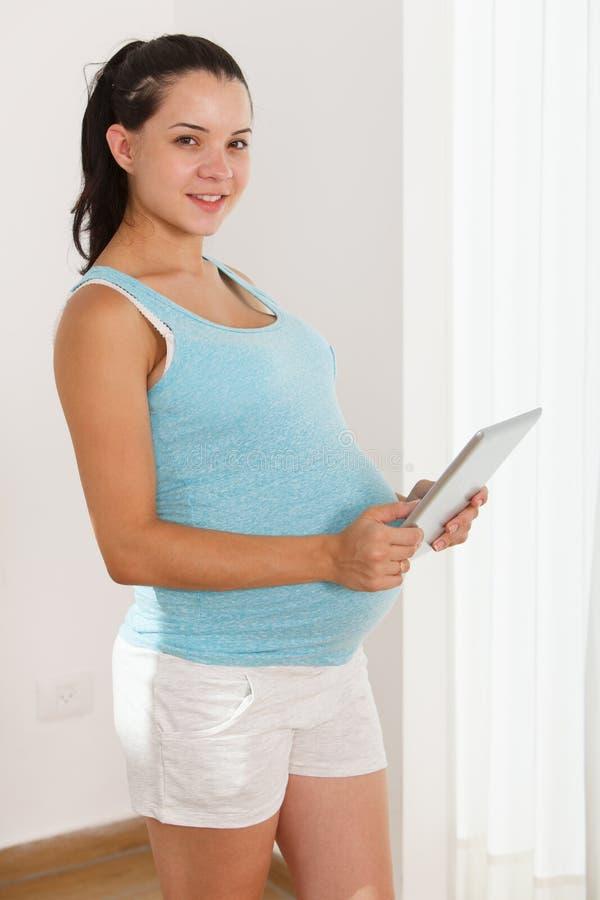 Donna incinta che tiene la compressa di Digital fotografia stock libera da diritti