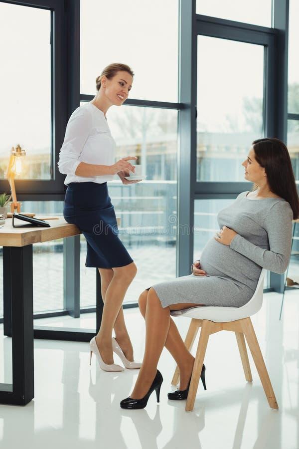 Donna incinta che tocca la sua pancia e un capo gentile che la esamina immagine stock libera da diritti