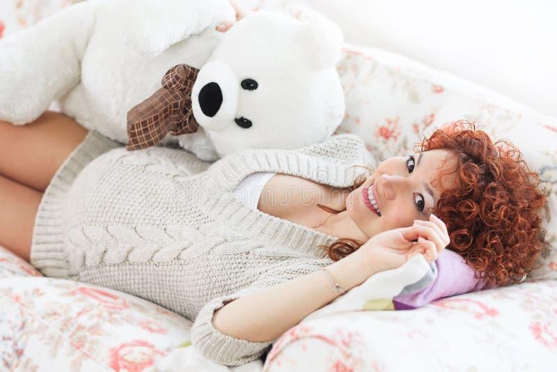 Donna incinta che tocca la sua pancia mentre trovandosi su un letto alla h immagini stock libere da diritti