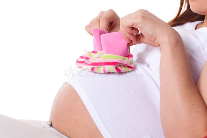 Donna incinta con i bambini \ 'bootees di s fotografia stock libera da diritti
