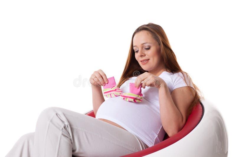 Donna incinta con i bambini \ 'bootees di s immagini stock