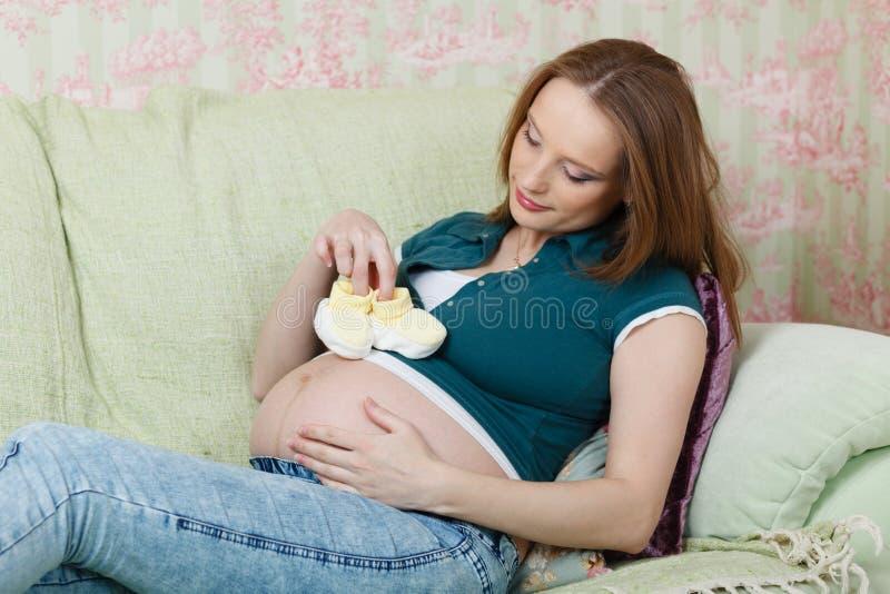 Donna incinta con i bootees dei bambini immagini stock libere da diritti