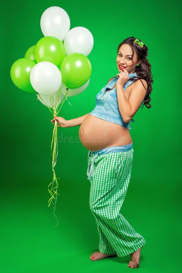 Donna incinta con i palloni su un fondo verde Esamina la sua pancia, nell'anticipazione immagini stock libere da diritti