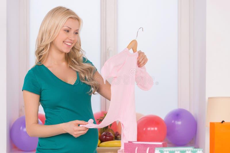 Donna incinta con i vestiti del bambino. fotografie stock