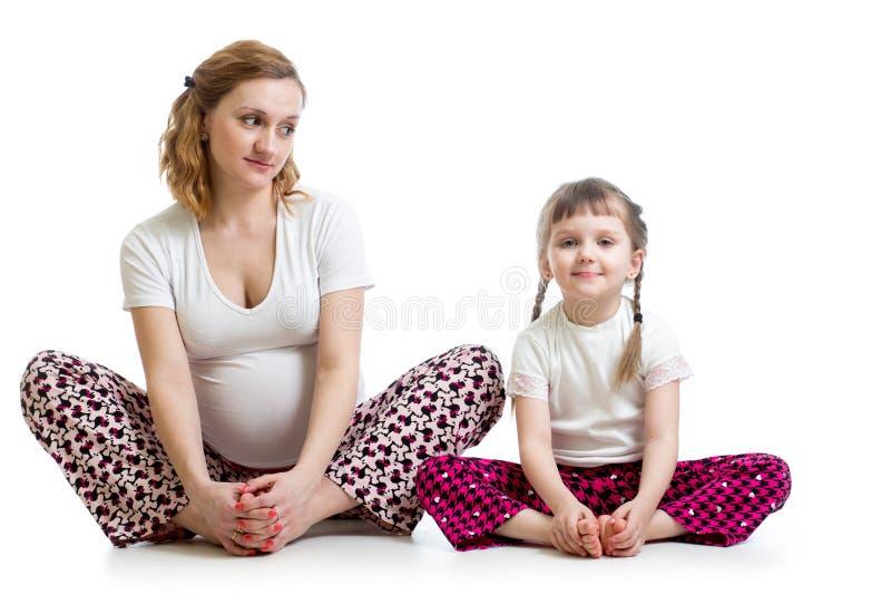 Donna incinta con il bambino che fa gli esercizi di yoga fotografia stock libera da diritti