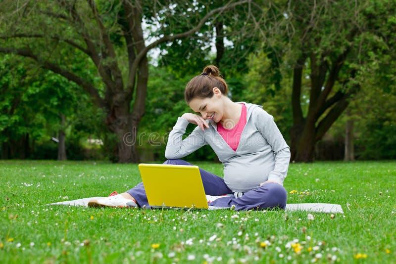 Donna incinta con il computer portatile immagine stock