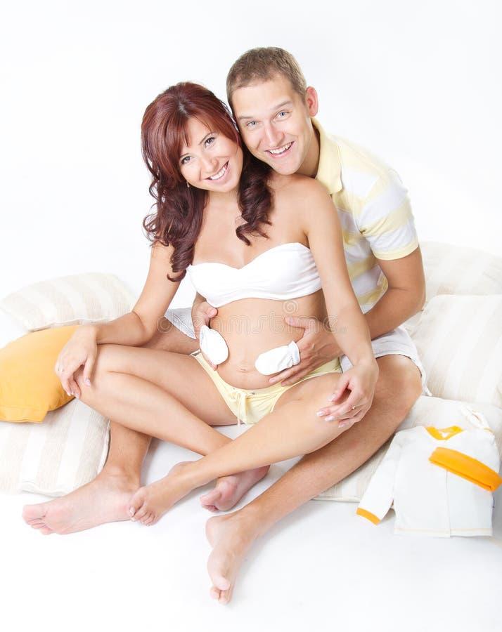 Donna incinta con il marito che gioca sopra la pancia immagine stock
