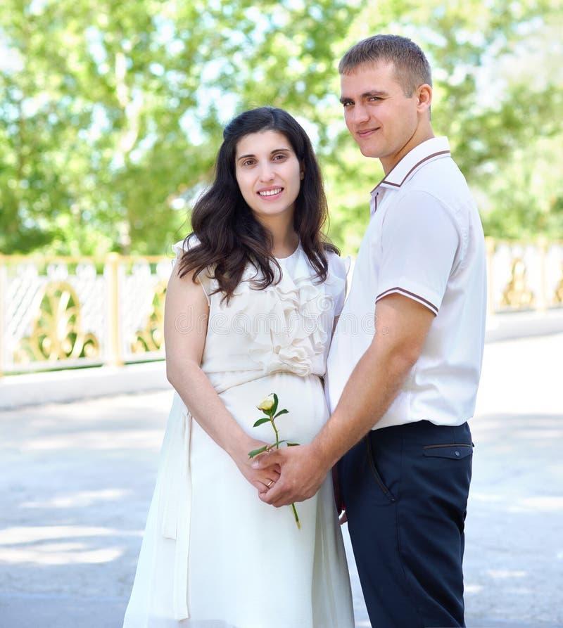 Donna incinta con il marito che posa nel parco della città, nel ritratto della famiglia, nella stagione estiva, nell'erba verde e immagine stock libera da diritti