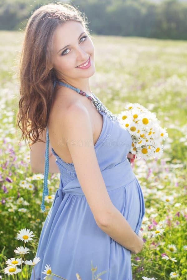 Donna incinta con il mazzo dei fiori della margherita fotografie stock libere da diritti