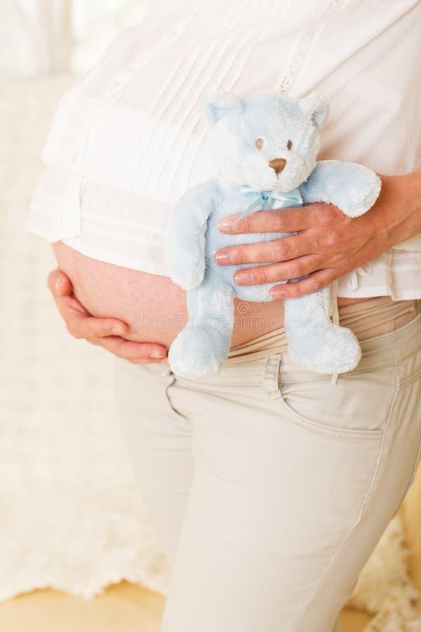 Donna incinta con l'orsacchiotto. immagine stock