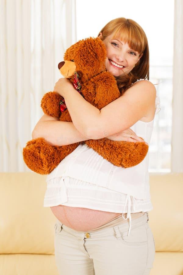Donna incinta con l'orsacchiotto. fotografia stock