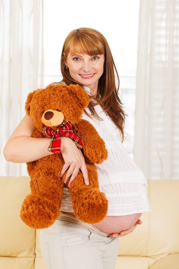 Donna incinta con l'orsacchiotto. fotografie stock libere da diritti