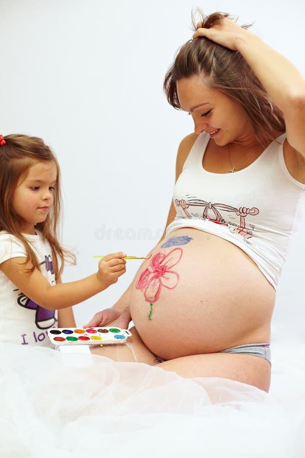 Donna incinta con la pancia sveglia della vernice della figlia immagine stock