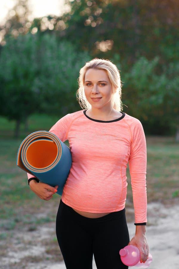 Donna incinta di forma fisica che sorride alla macchina fotografica fotografie stock