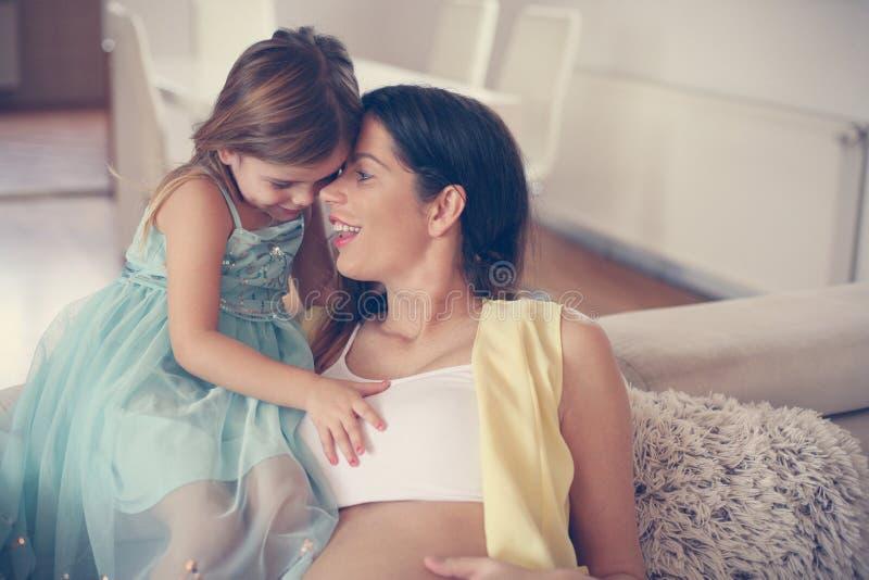 Donna incinta e la sua piccola figlia immagini stock