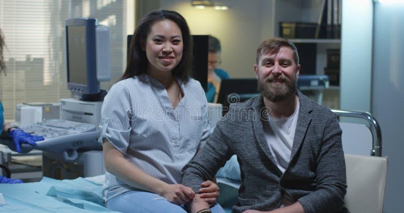 Donna incinta ed il suo ragazzo che sorridono alla macchina fotografica immagini stock