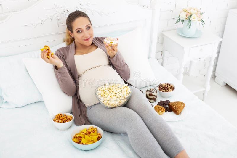 Donna incinta felice che inghiotte alimenti industriali immagine stock