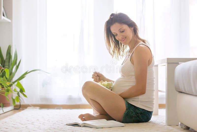 Donna incinta felice che mangia insalata a casa immagine stock