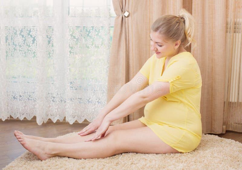 Donna incinta felice che si esercita e che allunga immagini stock