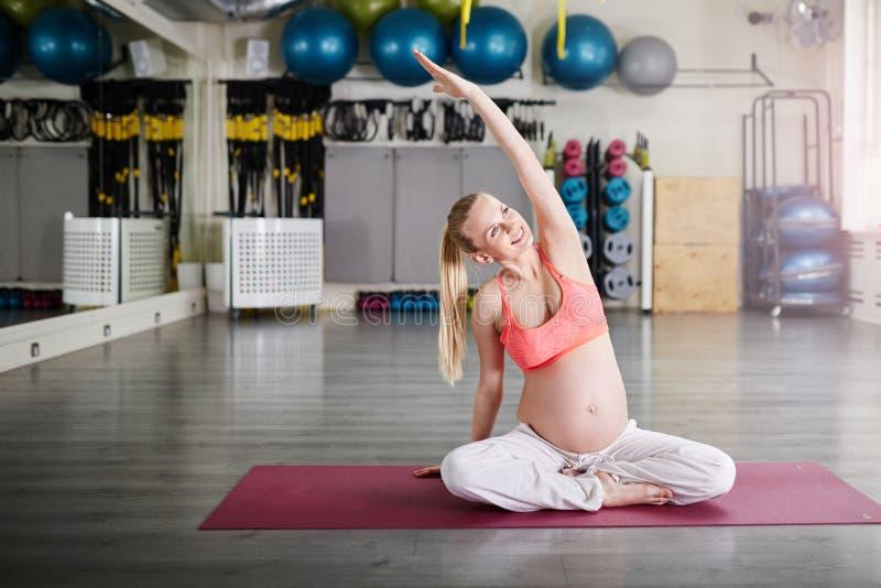 Donna incinta felice che si siede sull'yoga di addestramento del pavimento fotografie stock