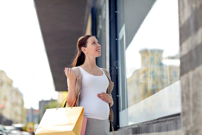 Donna incinta felice con i sacchetti della spesa alla città fotografia stock