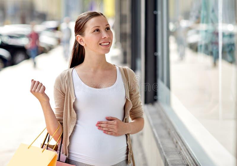 Donna incinta felice con i sacchetti della spesa alla città immagini stock