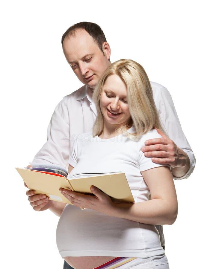 Donna incinta felice con il suo marito che legge un libro immagini stock libere da diritti