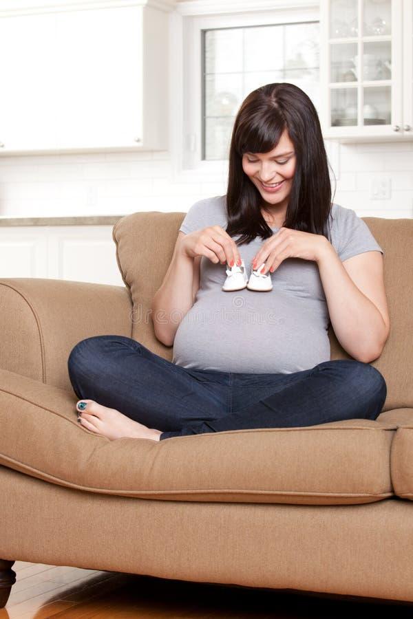 Donna incinta felice con le scarpe di bambino fotografie stock libere da diritti