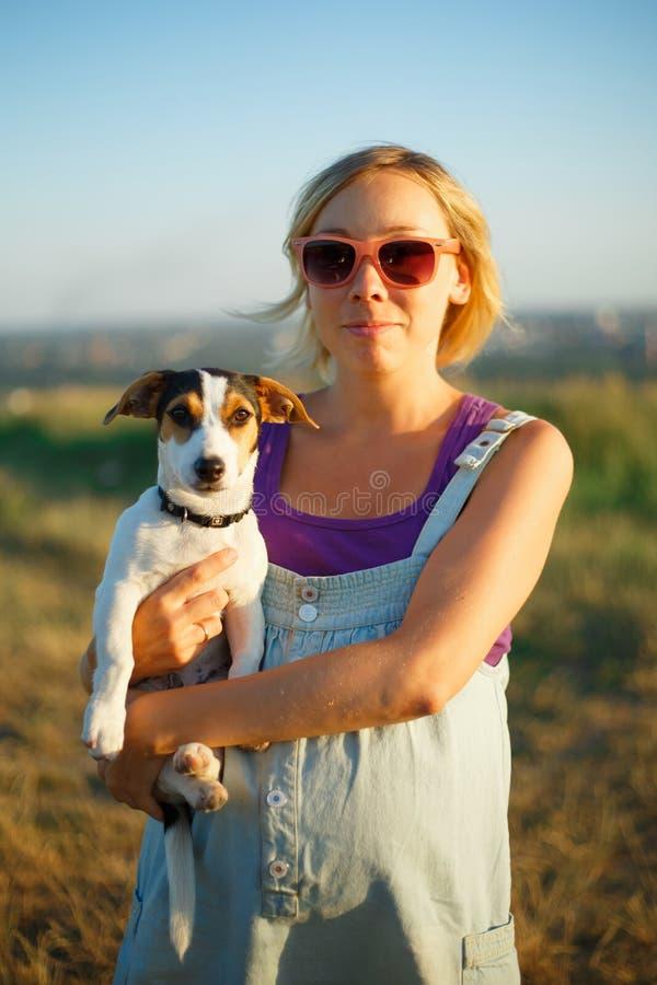 Donna incinta felice con un cane al tramonto fotografie stock