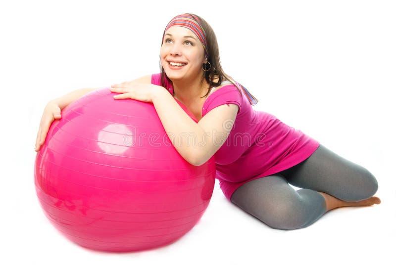 Donna incinta felice con una sfera di forma fisica fotografia stock