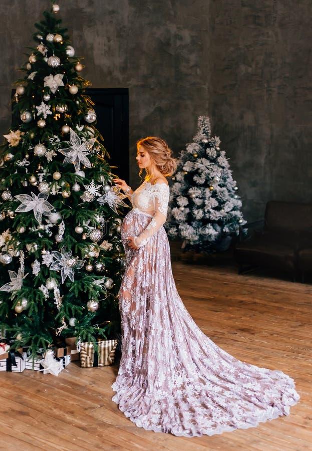 Donna incinta graziosa con capelli ordinati ricci stupefacenti biondi, portanti un vestito leggero traslucido dal pizzo bianco co fotografia stock libera da diritti