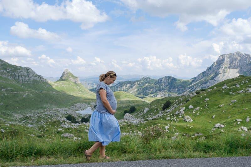 Donna incinta graziosa nei precedenti di un paesaggio della montagna immagine stock