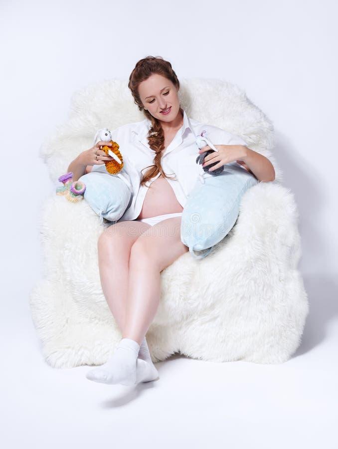 Donna incinta in poltrona immagini stock