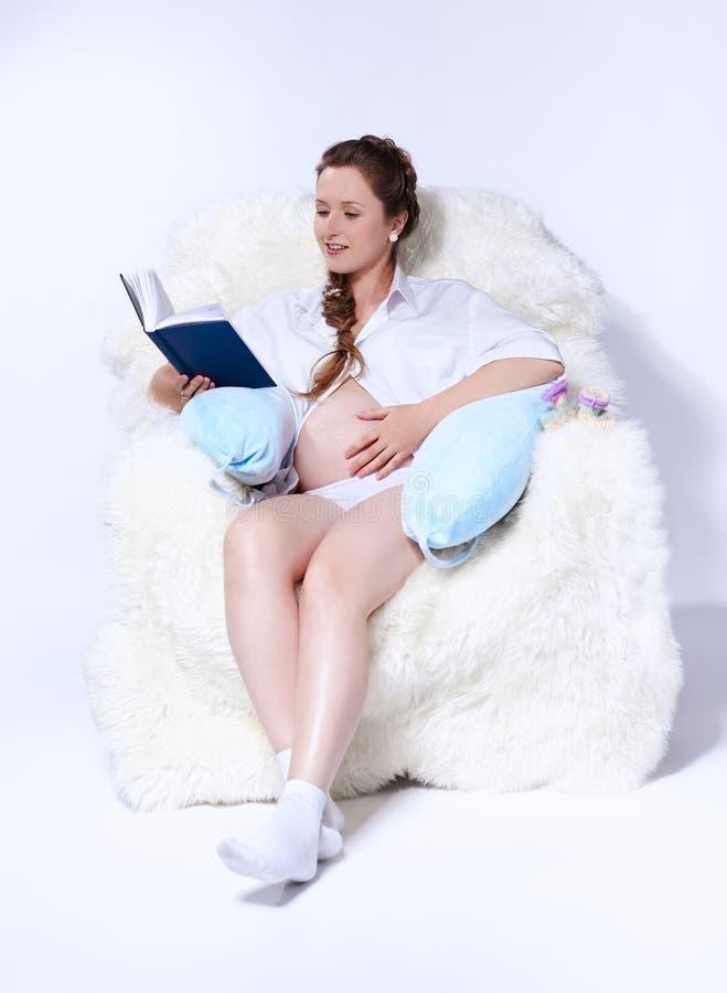 Donna incinta in poltrona fotografie stock