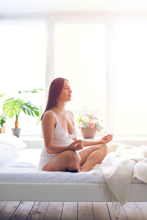 Donna incinta rilassata che fa meditazione in camera da letto fotografia stock