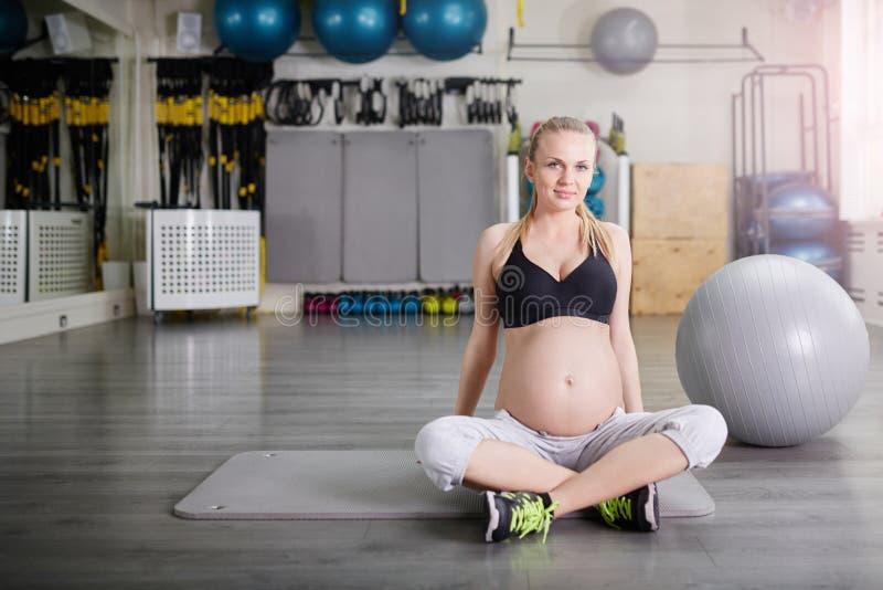Donna incinta sicura che si siede fornito di gambe trasversale fotografie stock libere da diritti
