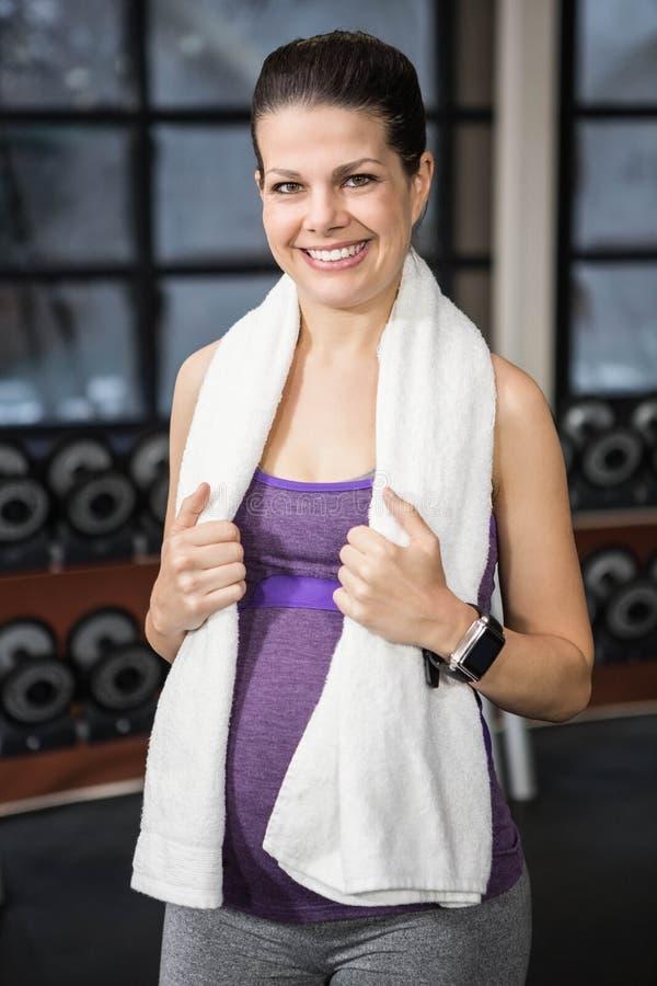 Donna incinta sorridente che sta con l'asciugamano intorno al suo collo fotografie stock libere da diritti