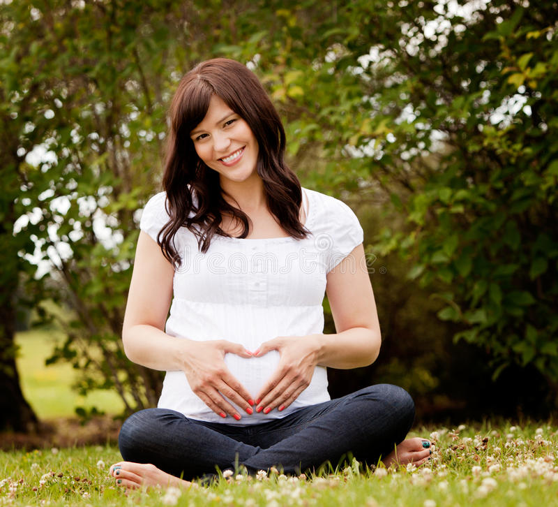 Donna incinta sorridente felice in parco fotografie stock libere da diritti